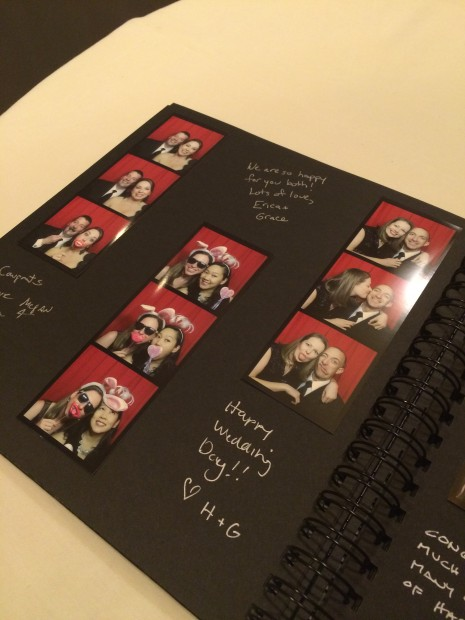 Wedding guests filling up the scrap book with photo booth photos at a recent wedding in New York, NY